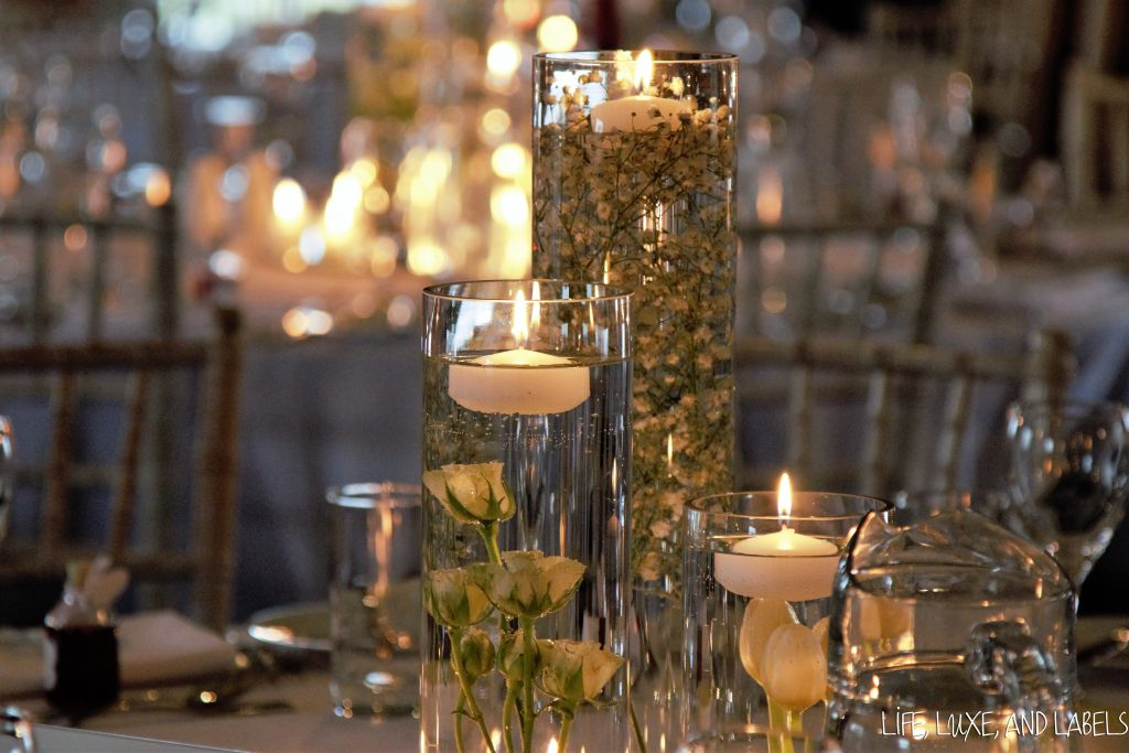 White candles floating in a jar filled with white roses and green foliage